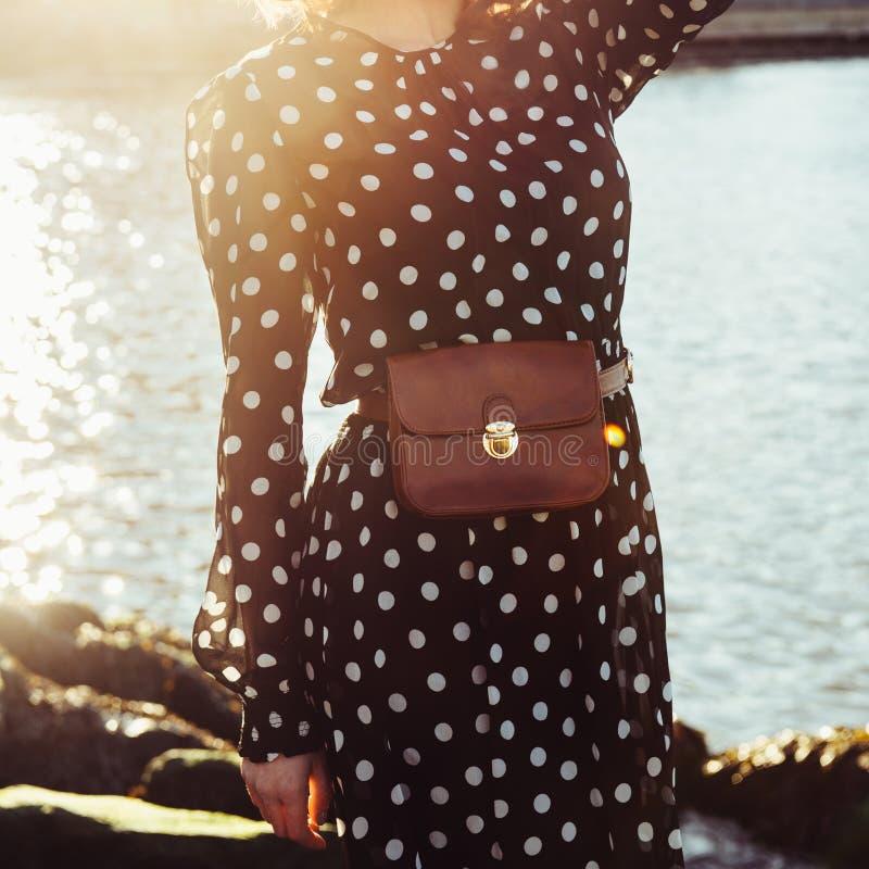 Zufällige weibliche Ausstattung des Frühlingssommers mit langem schwarzem Kleid in den Tupfen mit lederner Brauengeldbeutel-Gurtt stockfotos
