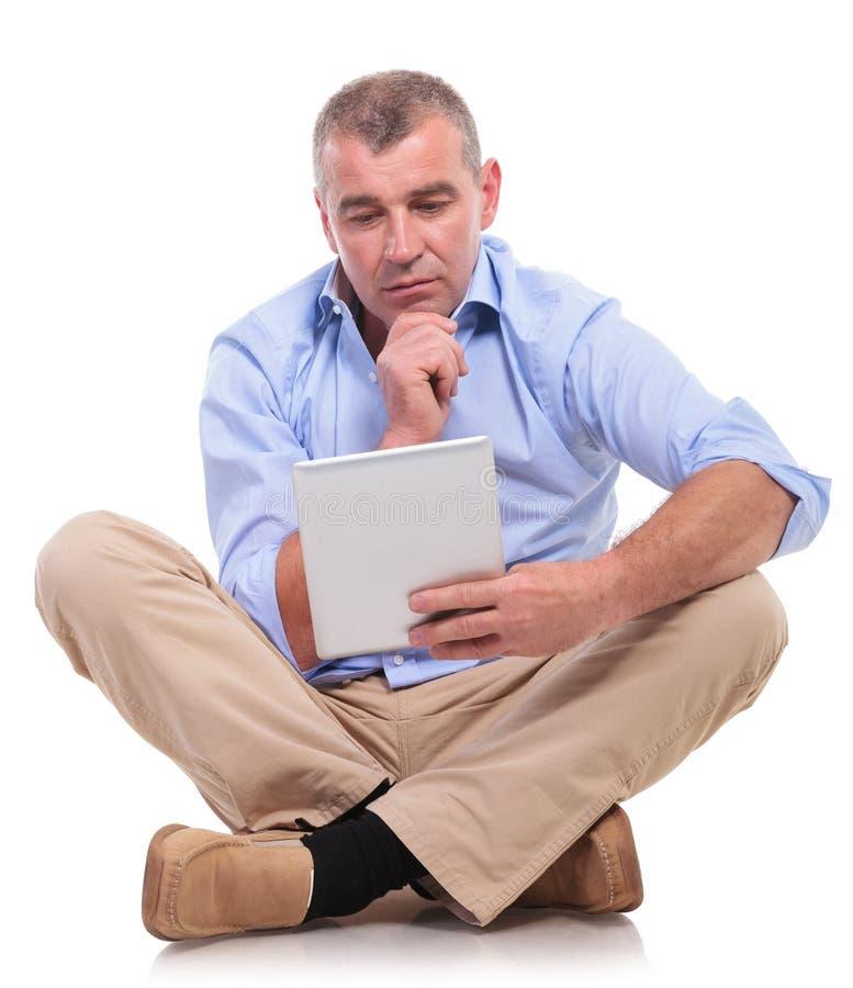 Zufälliger alter Mann sitzt und betrachtet nachdenklich Auflage stockfoto