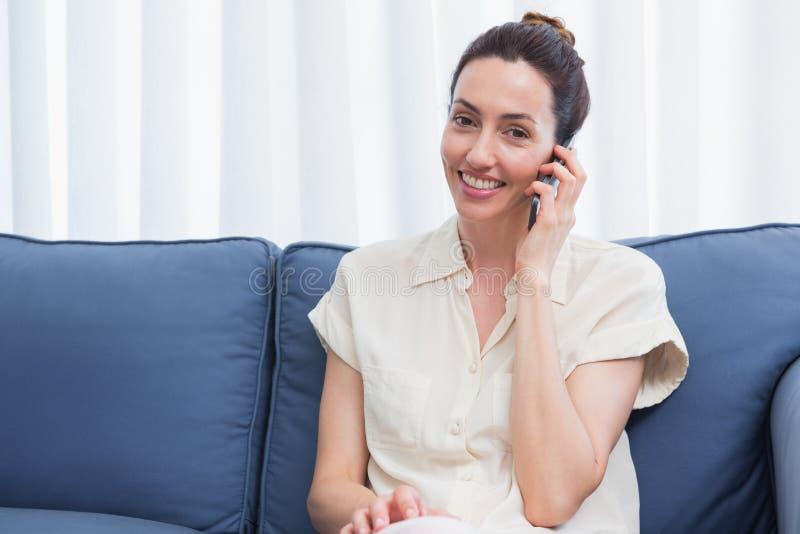 Zufälliger Brunette, der Telefonanruf auf Couch macht lizenzfreie stockfotografie