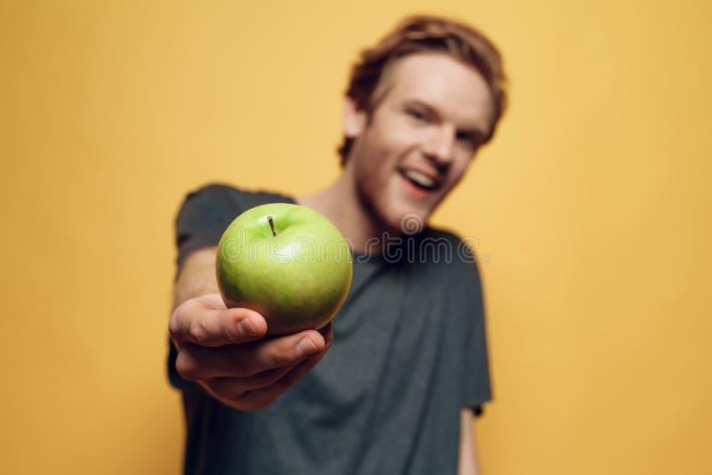 Zufälliger junger bärtiger Mann, der grünes Apple hält lizenzfreie stockbilder