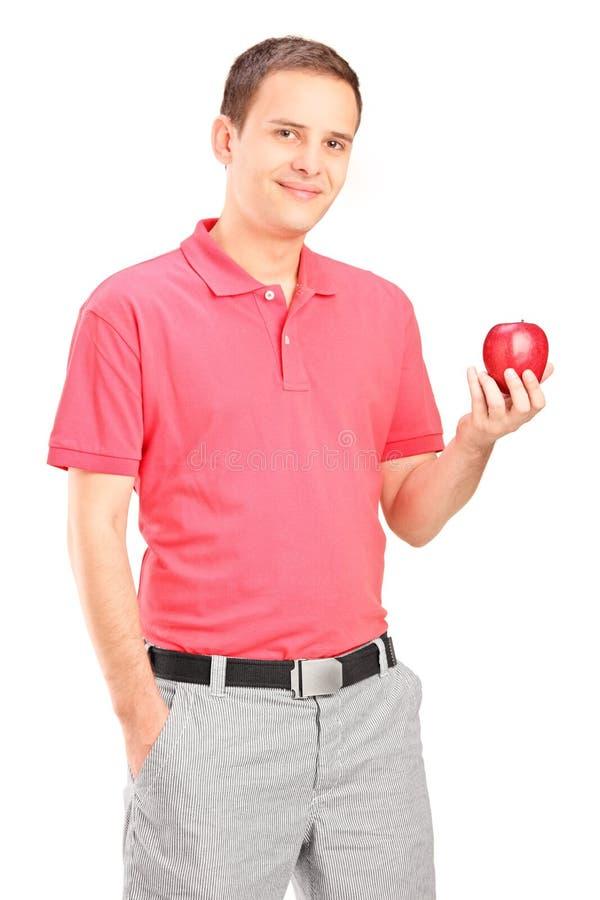 Zufälliger junger Mann, der einen Apfel hält stockfoto