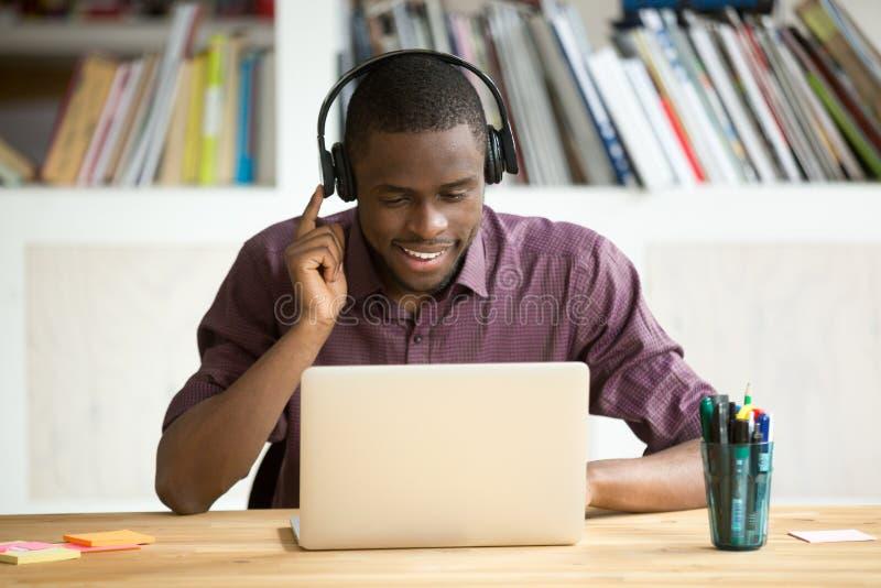 Zufälliger lächelnder Büroangestellter in den Kopfhörern, die Laptopstörungsbesuch betrachten lizenzfreie stockfotografie