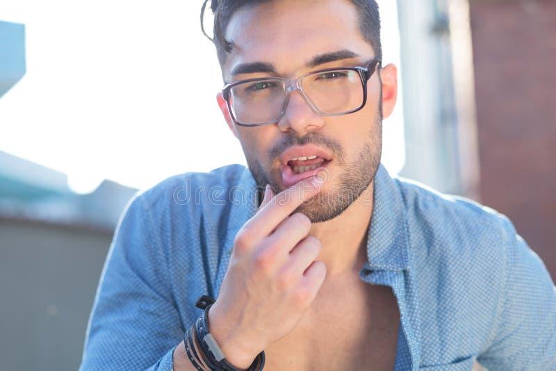 Zufälliger Mann berührt seine untere Lippe stockbild