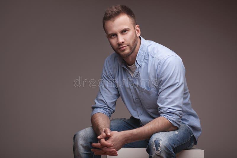 Zufälliger Mann, der auf einem Würfel sitzt stockfotos