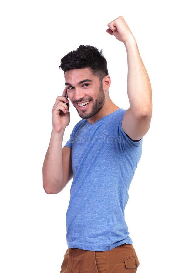 Zufälliger Mann, der Erfolg bei der Unterhaltung am Telefon feiert stockfotos