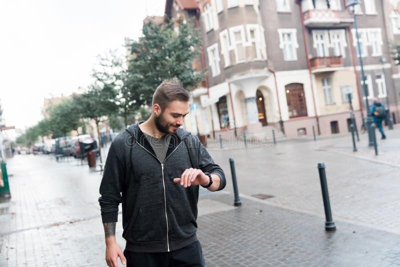 Zufälliger Mann, der seine Uhr auf der Straße betrachtet stockfotografie