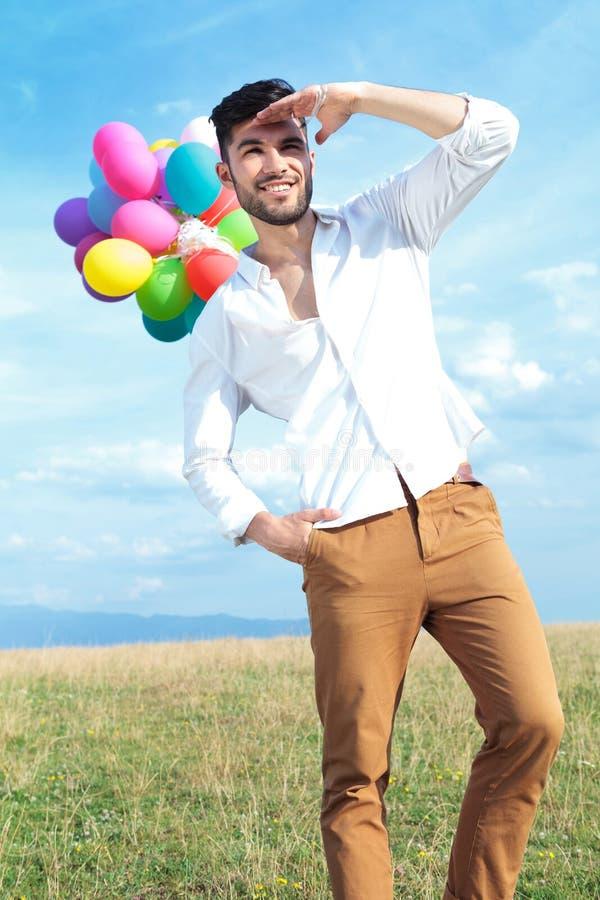 Zufälliger Mann mit Ballonen schaut weit weg lizenzfreie stockfotos