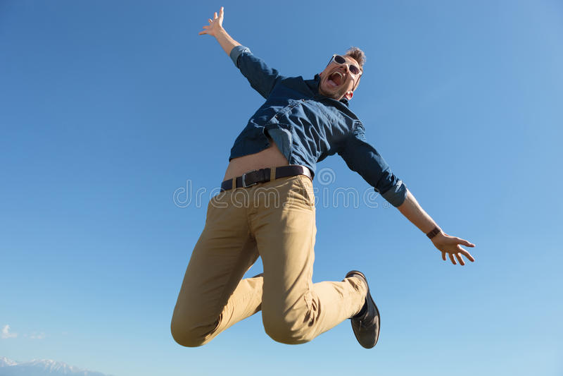 Zufälliger Mann springt in mitten in der Luft stockfotografie