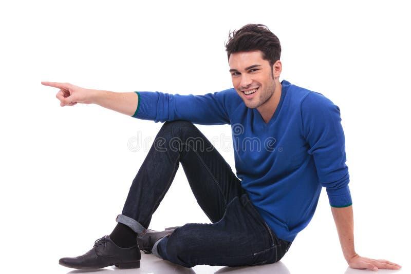 Zufälliger Mann zeigt auf seine Seite beim Sitzen lizenzfreie stockbilder
