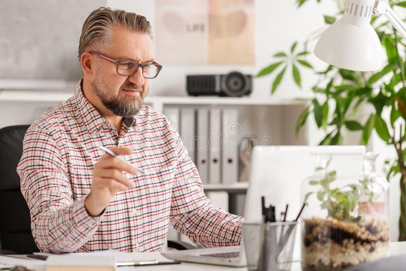 Zufälliger schauender hübscher Unternehmensmanager in seinem Büro lizenzfreie stockfotos