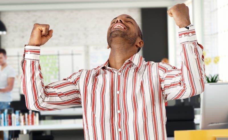 Zufälliger schwarzer Mann, der Erfolg im Büro feiert lizenzfreie stockbilder