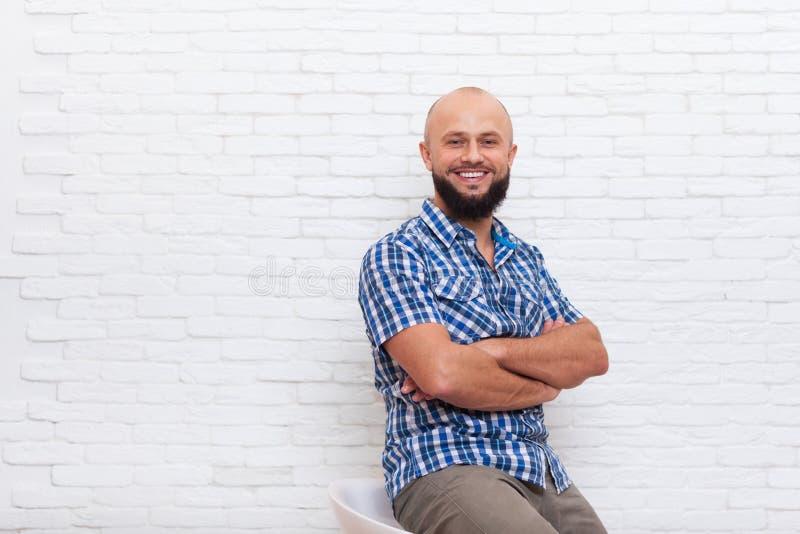 Zufälliges bärtiges Geschäftsmann-sitzendes lächelndes gefaltetes Handbüro stockfoto