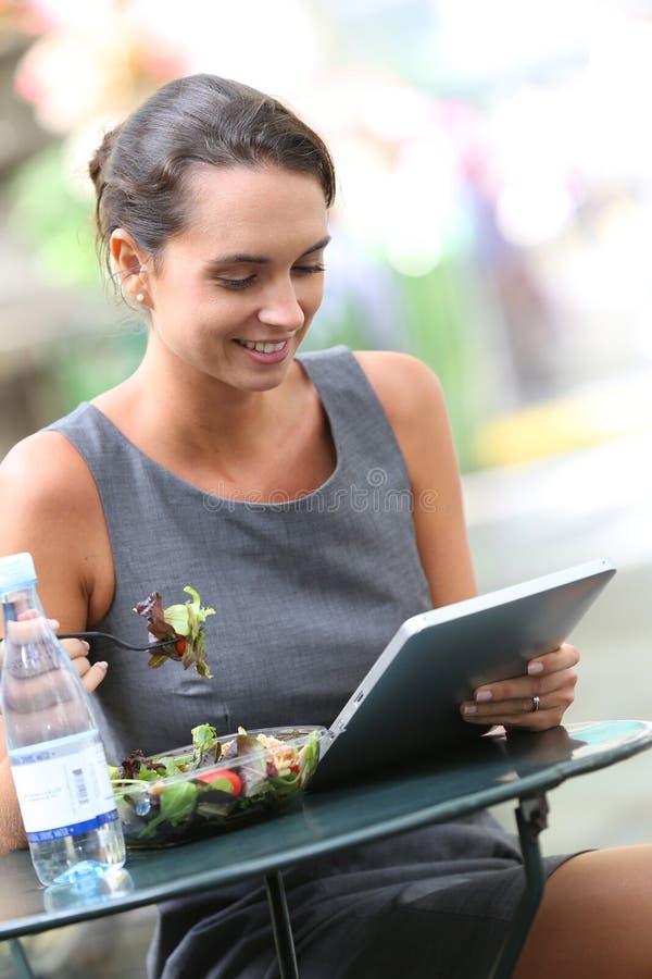 Zufälliges beschäftigtes wbusinesswoman, welches das Mittagessen isst und an Tablette arbeitet stockfotos