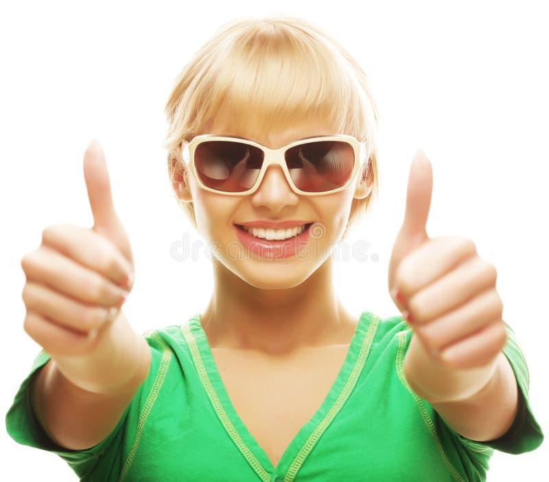 Zufälliges Mädchen, das sich Daumen und das Lächeln zeigt stockfoto