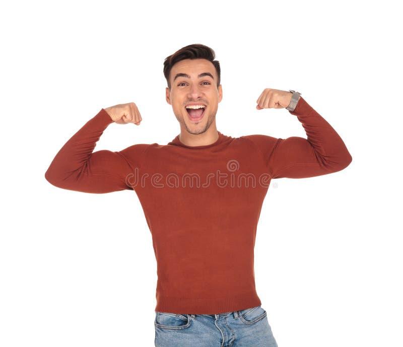 Zufälliges Mannschreien der Freude beim Biegen seines Bizepses lizenzfreie stockbilder