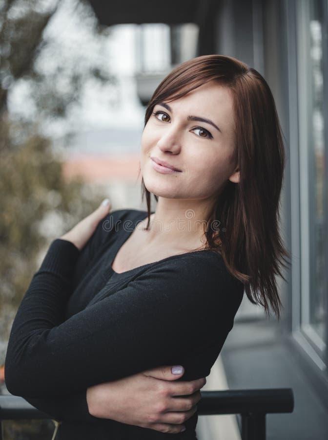 Zufälliges Porträt des netten und positiven Mädchens auf dem Balkon mit Park auf Hintergrund Hübsche braune behaarte Frau, die zu stockfoto