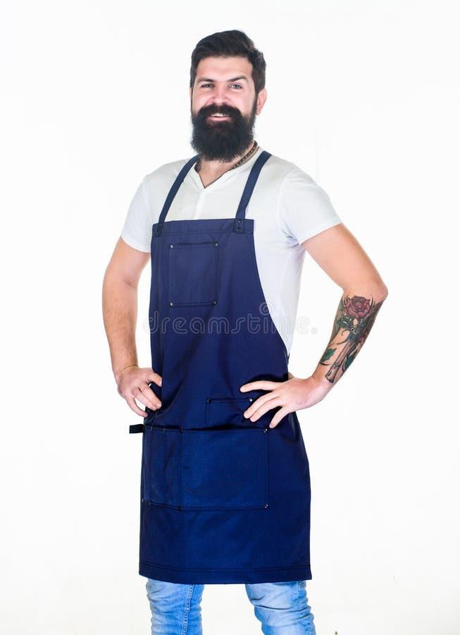 Zuf?llig und stilvoll Glücklicher Koch, der Schutzblech mit Taschen kochend trägt Kochen Sie im Schutzblech, das Hände auf Hüften lizenzfreie stockfotografie