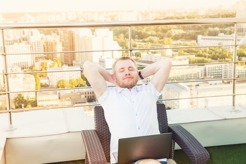 Zufrieden gestellt mit der Arbeit erledigt Nettes Händchenhalten des jungen Mannes hinter Kopf und halten Augen beim Sitzen gesch lizenzfreies stockbild