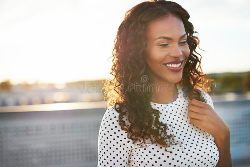 Zufrieden gestellte junge Frau mit einem glücklichen Lächeln lizenzfreie stockbilder