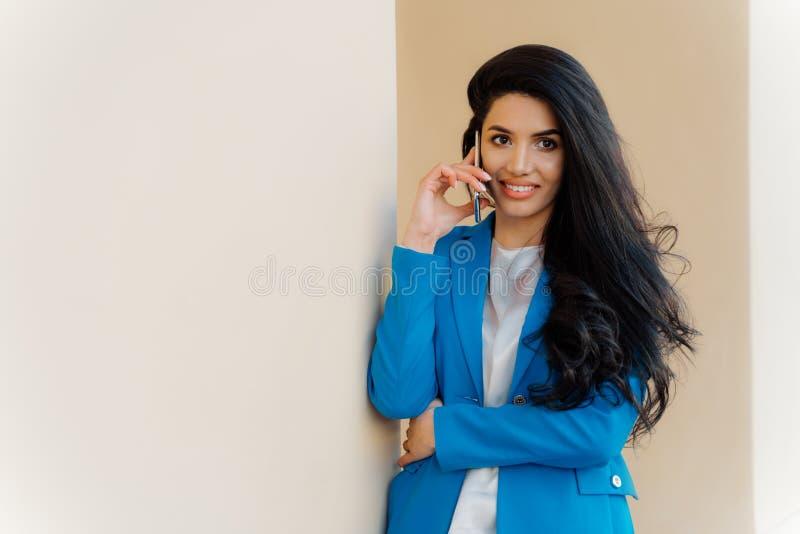 Zufriedene brunette Geschäftsdame nennt auf Smartphonegerät, Buchkarten für Auslandsreise, macht das positive Gespräch, gekleidet lizenzfreie stockbilder