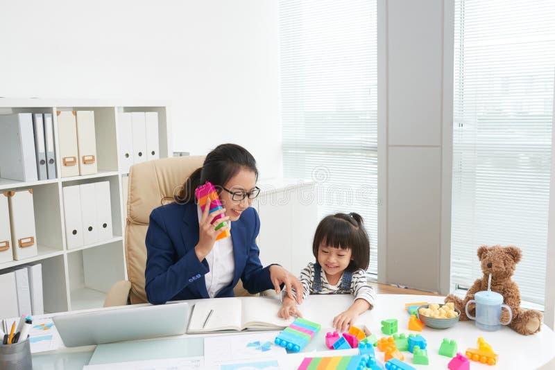 Zufriedene ethnische Frau mit Mädchen bei der Arbeit lizenzfreies stockfoto