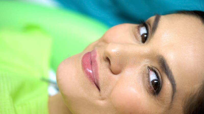 Zufriedene Frau nach Mikrobeschaufelungsverfahren im Kosmetikerbüro, Schönheit lizenzfreie stockfotografie