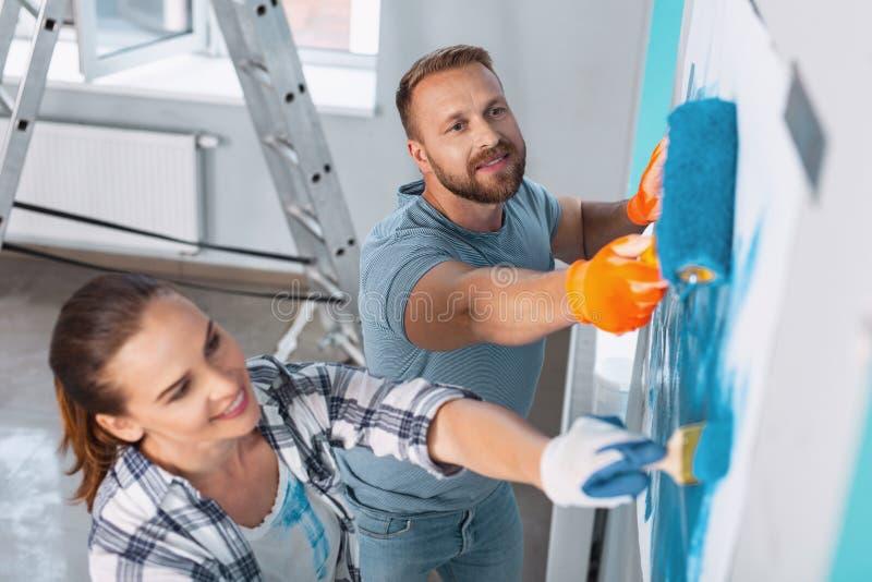 Zufriedene Maler, die Erneuerungen in der Wohnung tun lizenzfreie stockfotos