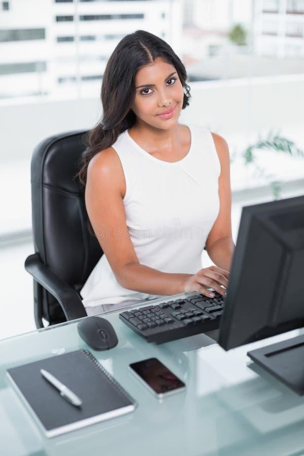 Zufriedene nette Geschäftsfrau, die am Computer arbeitet stockbild
