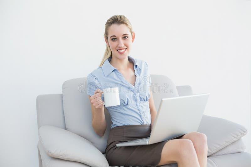 Zufriedene reizende Geschäftsfrau, die ihr Notizbuch hält eine Schale verwendet stockfoto