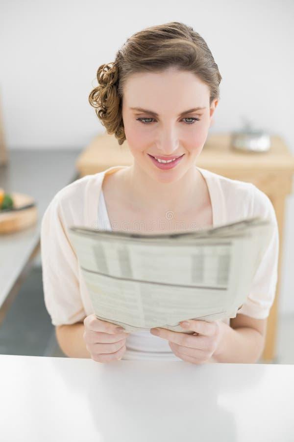 Zufriedene Schönheit, die in der Küchenlesezeitung sitzt lizenzfreies stockfoto