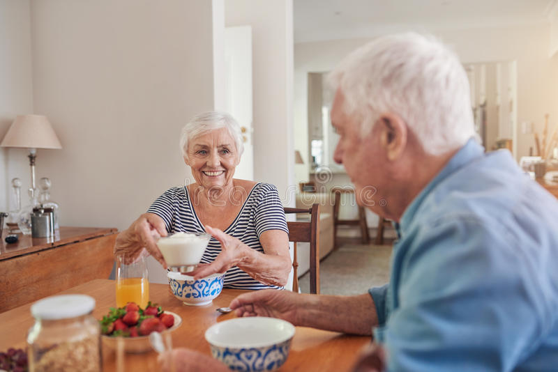Zufriedene Senioren, die zusammen ein gesundes Frühstück zu Hause essen stockfotografie