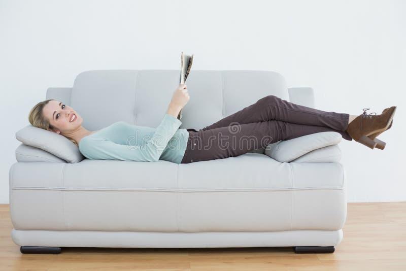 Zufriedene zufällige Frau, welche die Zeitung liegt auf Couch hält lizenzfreie stockbilder