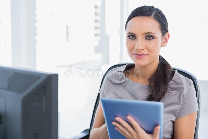 Zufriedener attraktiver Sekretär, der Tabletten-PC verwendet