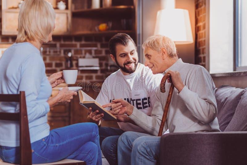 Zufriedener Freiwilliger, der ein Buch für Pensionäre liest stockfoto