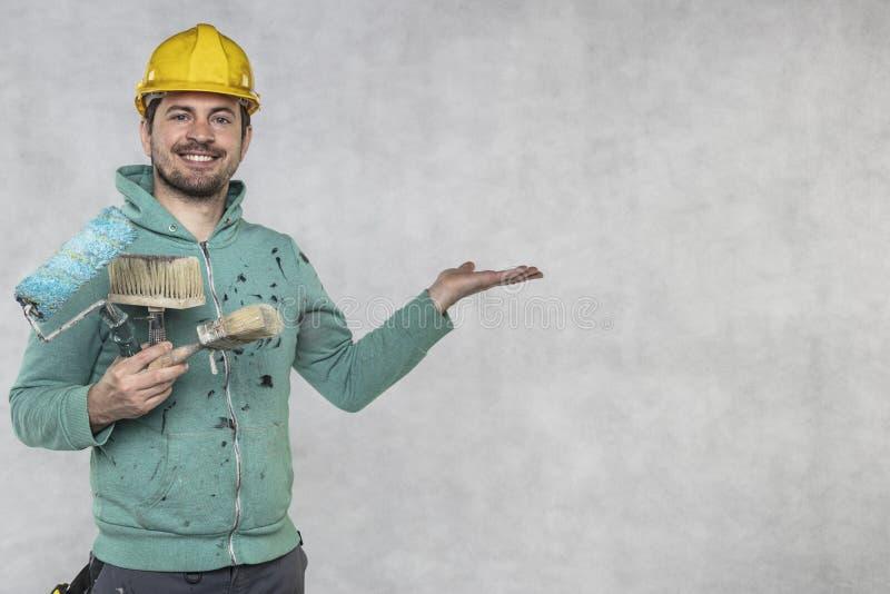 Zufriedener Maler zeigt Kopienraum über der Hand und malt Werkzeuge stockbild