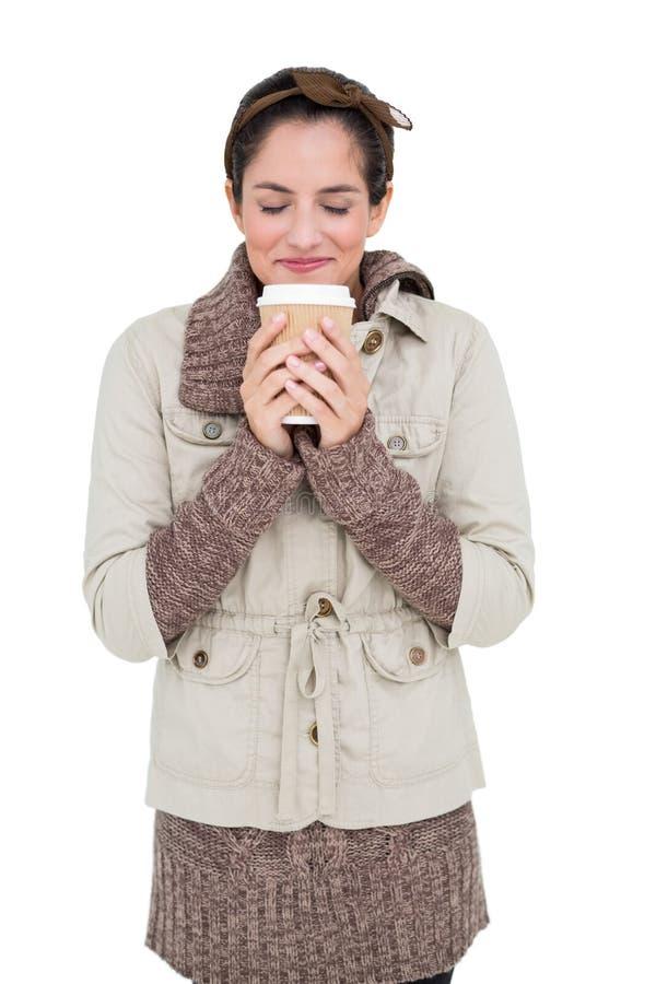 Zufriedener netter Brunette auf die Wintermode, die Wegwerfschale hält stockfotografie
