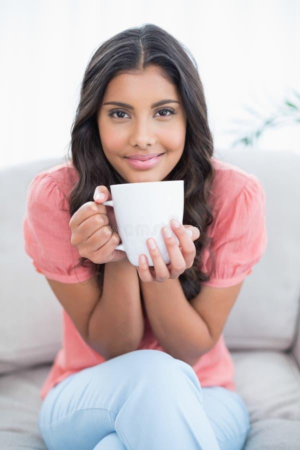 Zufriedener netter Brunette, der auf der Couch hält Becher sitzt stockfoto