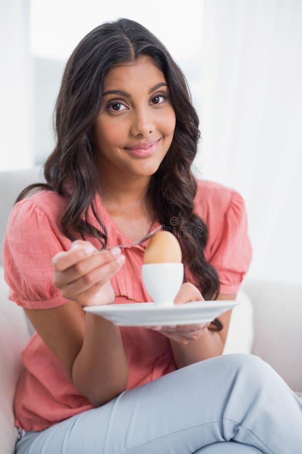 Zufriedener netter Brunette, der auf der Couch hält hart gesotten Ei sitzt lizenzfreies stockbild