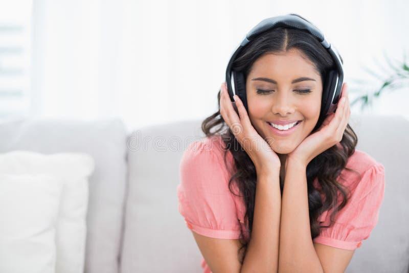 Zufriedener netter Brunette, der auf der Couch hört Musik mit geschlossenen Augen sitzt stockbilder