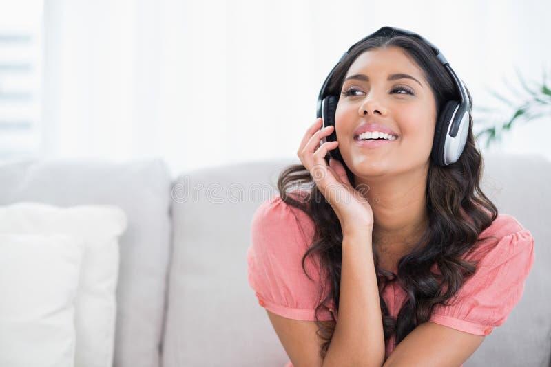 Zufriedener netter Brunette, der auf der Couch hört Musik sitzt lizenzfreies stockfoto