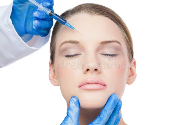 Zufriedenes attraktives vorbildliches, botox Einspritzung auf der Stirn habend lizenzfreies stockbild