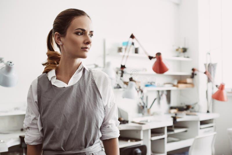 Zufriedengestellt mit ihrem Job Nahes hohes Porträt der überzeugten und jungen weiblichen Juwelierstellung an ihrer Schmuckwerkst lizenzfreies stockfoto