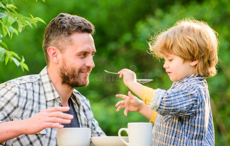 Zufuhrsohnkörper Vati und Junge drau?en essen und sich einziehen Weisen, Gewohnheiten der gesunden Ern?hrung zu entwickeln Ziehen lizenzfreies stockbild