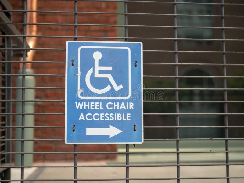 Zugängliches Zeichen des Rollstuhls, das rechts draußen draußen in Position gebracht auf Drahtgeländer zeigt stockfotografie