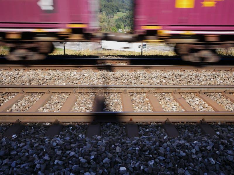 Zug überschreitet mit Geschwindigkeit vor einer Autobahn stockfotos