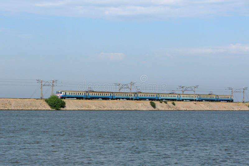 Zug auf Dammlinie an Kakhovka-Wasserreservoir, Ukraine stockbild