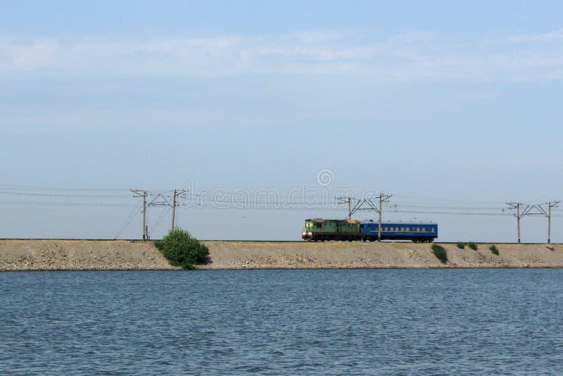 Zug auf Dammlinie an Kakhovka-Wasserreservoir, Ukraine stockfotos