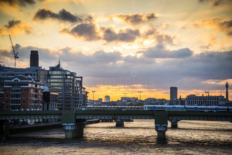 Zug, der über Kanonen-Straßenbahn-Brücke bei Sonnenuntergang, London, Großbritannien überschreitet lizenzfreie stockbilder