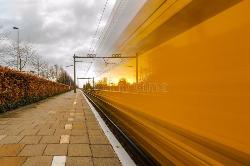 Zug der niederländischen Eisenbahnen führt die Plattform einer Bahnstation in Delft an der hohen Geschwindigkeit lizenzfreie stockfotos