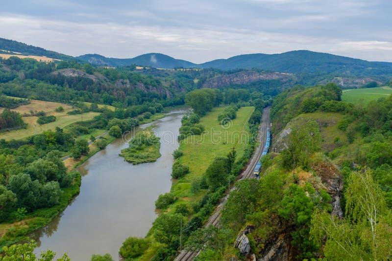 Zug in einem Tal durch einen Fluss stockfotografie